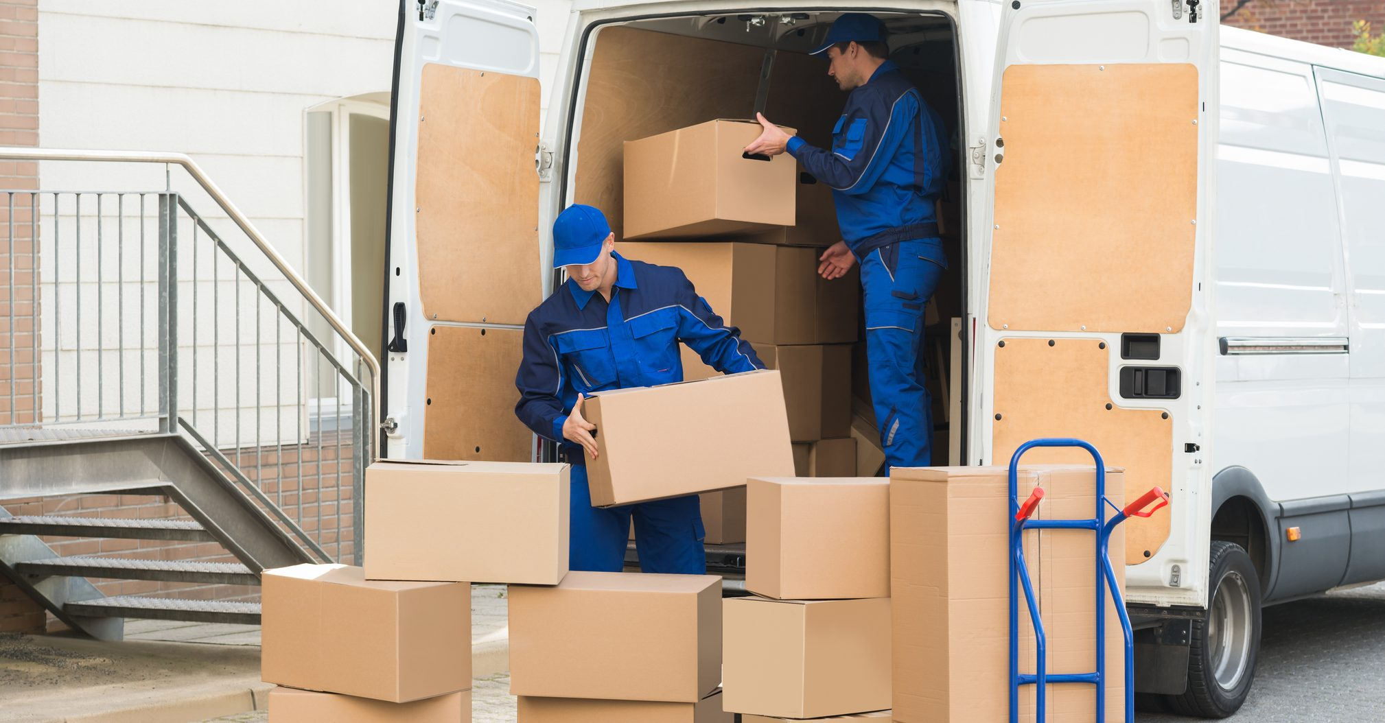 delivery-men-unloading-boxes-on-street-77509344-e1514826845397